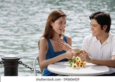 Couple sitting at outdoor cafe, man giving woman a gift