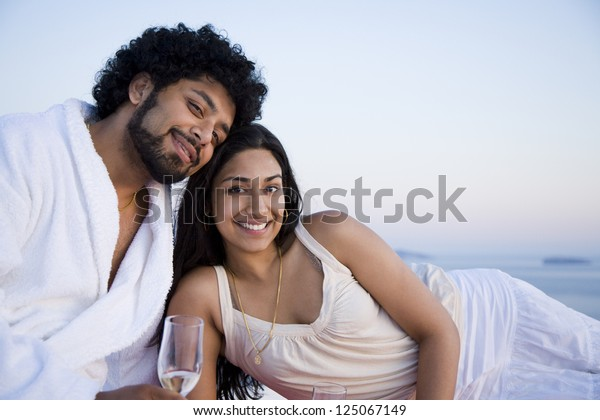 Couple sitting outdoors with champagne flutes and scenic background smiling and snuggling