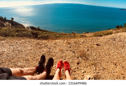 Couple Sitting Overlooking The Ocean from a Cliff while Hiking on Sunny Summer Day Together
