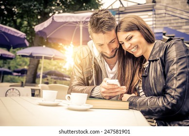 Couple sitting at restaurant table taking a self portrait with phone - Friends in a bar looking at cell phone