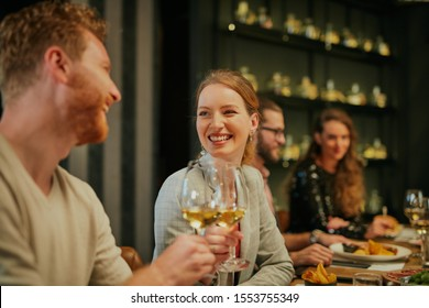Couple sitting in restaurant with their friends and toasting with wine.