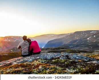 A couple sitting at the rock and watching the sunset. Sun sets behind the mountains. Sky is full of colors. Girl is leaning on the boy. Happiness, passion and love joined with the pursue of travel.