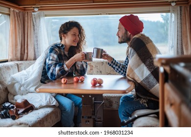 Couple sitting at a table in a motorhome and drinking tea.