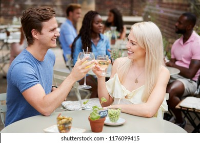 Couple Sitting At Table In Pub Garden Making A Toast Together