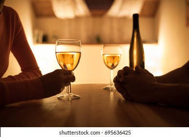 Couple sitting together enjoying a glass of wine a conversation.