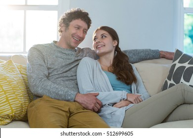 Couple sitting together on sofa at home