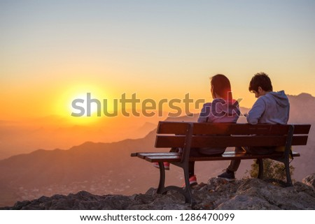 couple-sitting-together-watching-sunset-