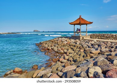 Couple sitting in traditional Balinese gazebo with ocean view. Candidasa, East Bali