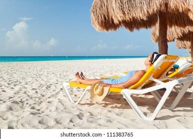 Couple sitting under palm tree at Caribbean Sea