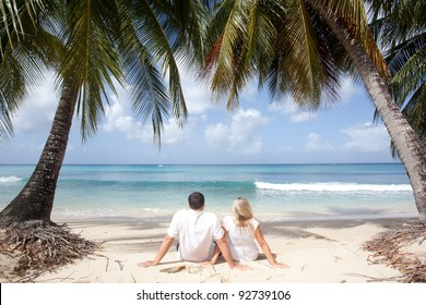 couple sitting under the palm trees in tropical beach