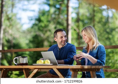Couple sitting at wooden table on country house balcony with open laptop, talking cheerfully and laughing over tea