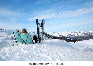 Couple of skiers relaxing in long chairs