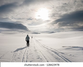 Couple skiing in a flat terrain towards the sun during an overcast day in the norwegian mountains at easter