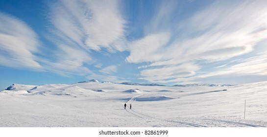 Couple skiing in a groomed curved double ski track with mountain summits and a characteristic cloud formation in the background in the norwegian mountains at easter