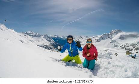A couple in skiing outfits playing in the powder snow. They are throwing snow balls and laughing out loud, play time. Endless ranges of snow caped mountains in the back. Mölltaler Gletscher, Austria.