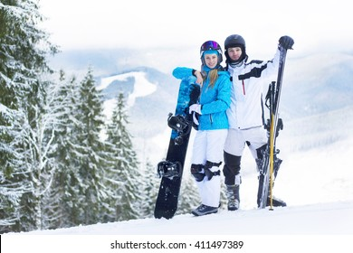Couple skiing and snowboarding outside in the mountains