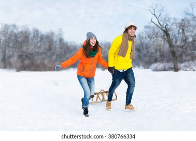 Couple with sled in snow