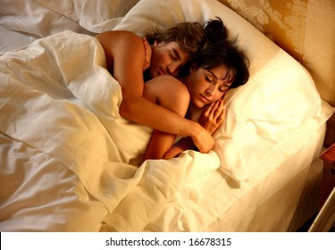 a couple sleep in a bed