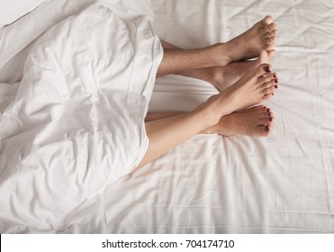 Couple sleeping in bed. two feet in bed looking out from under a blanket.