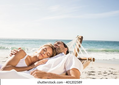 Couple sleeping in hammock on the beach