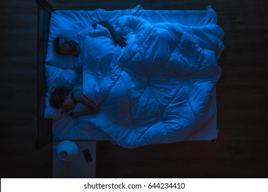 The couple sleeping on a bed. Evening night time. View from above