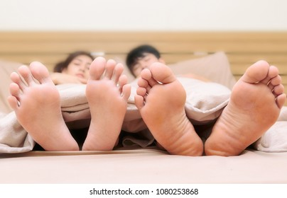 couple is sleeping on bed . Focus on their bare feet
