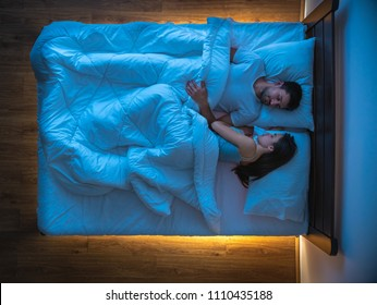 The couple sleeping on the bed. view from above, evening night time