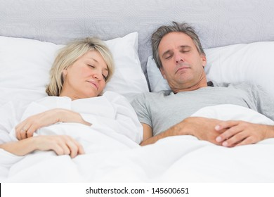 Couple sleeping peacefully in their bed at home in bedroom