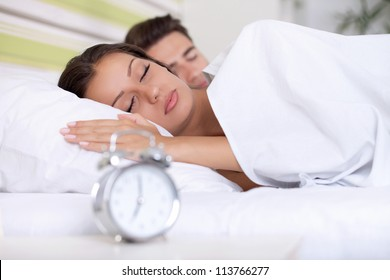 couple sleeping together in bed with  alarm clock