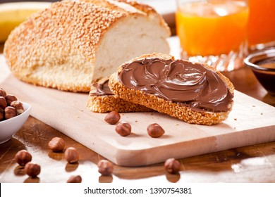 Couple of slices of bread with nutella and some fruit juice