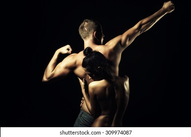 Couple of slim stripped girl embracing young boy with sexy strong muscular attractive body with raised arms and standing on studio black background, horizontal picture