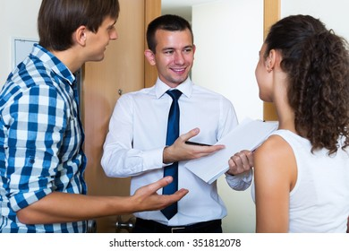 Couple and smiling agent with commercial documents near door