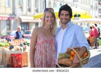 couple smiling blissfully at market
