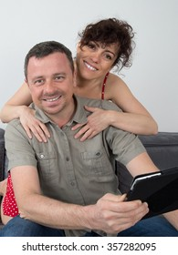 Couple and smiling at the camera at home in living room
