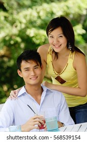 Couple smiling at camera, woman standing behind man, hand on shoulder
