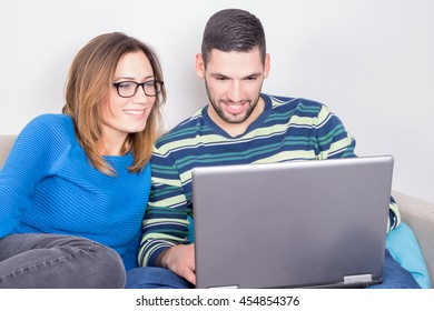 Couple smiling at a laptop