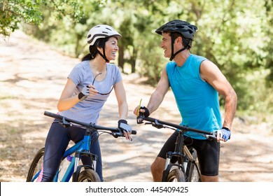 Couple smiling and looking each other on their bikes