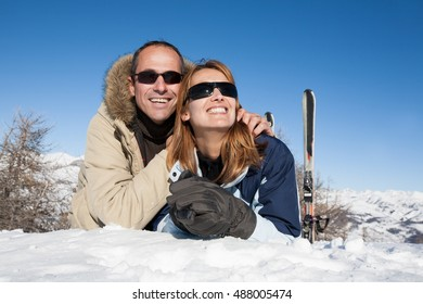 couple smiling in the snow in the sun
