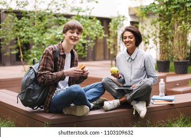 Couple of smiling students sitting on bench with sandwich and green apple and happily looking in camera while spending time together in courtyard of university