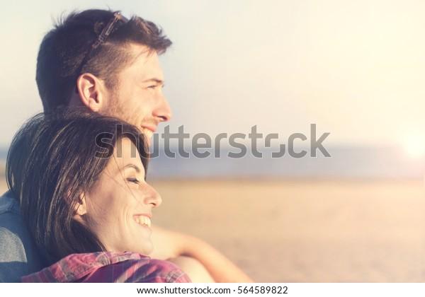 couple souriant parlant devant le coucher du soleil