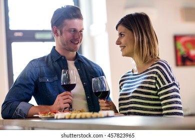 Couple smiling while holding wineglass at bar counter