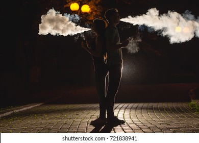 The couple smoke an electric cigarette on the dark alley. night time