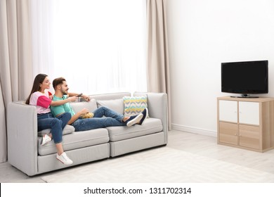 Couple with snack watching TV on sofa together at home. Space for text