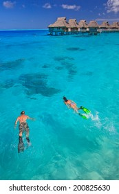 Couple snorkeling in the blue lagoon,   Bora Bora, French Polynesia, South Pacific