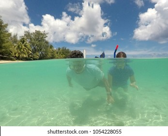 Couple snorkelling in clear tourquise lagoon water in Rarotonga, Cook Islands. Real people. Copy space