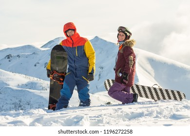 Couple snowboarding freeriders man and a woman go with snowboards on the ridge