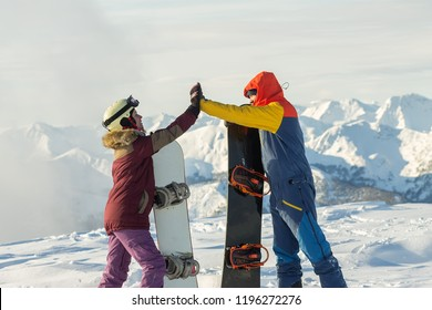 Couple snowboarding freeriders man and a woman give five with snowboards