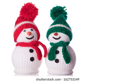 couple of snowman with red and green hat and scarf