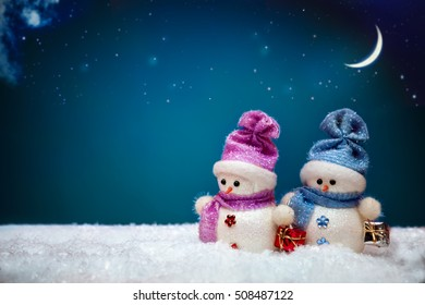Couple of snowmen on blue winter background with snowflakes