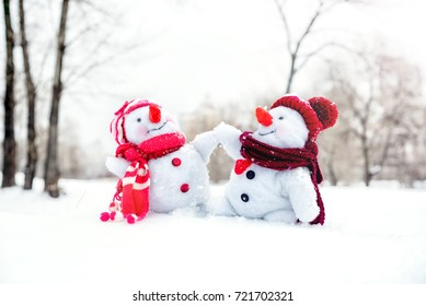Couple of snowmen taking hand of each other